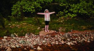 A happy girl playing on the bank of the River Breamish, Northumberland. (Copyright Northumberland National Park Authority).