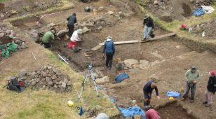 Coquetdale Community Archaeology volunteers working on the exposed remains of a medieval structure at Barrowburn. The group uncovered a high-quality paved floor, suggesting this site was built by the monks from Newminster Abbey in Morpeth.