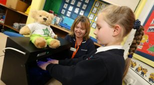 Chris Finch, infection prevention nurse at Nuffield Health Newcastle Hospital teaches a child from Bothal Primary School in Ashington about the importance of good hand hygiene.