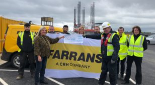 Jill Watkin, philanthropy manager at Blyth Star Enterprises accepts funds raised by Stuart McEwan, site foreman and the team at Farrans.